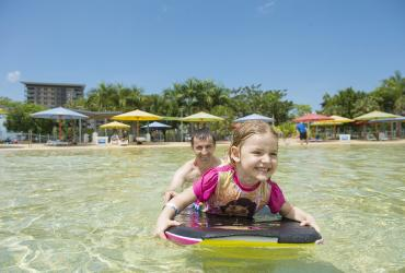 Young girl on paddle board while Dad pushes her through the water