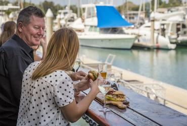 Man and woman enjoying a burger by the water