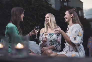 Three women enjoying a glass of wine in an alfresco setting