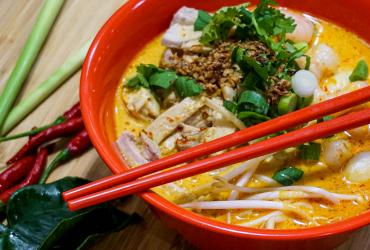 A bowl of laksa with chopsticks and spoon