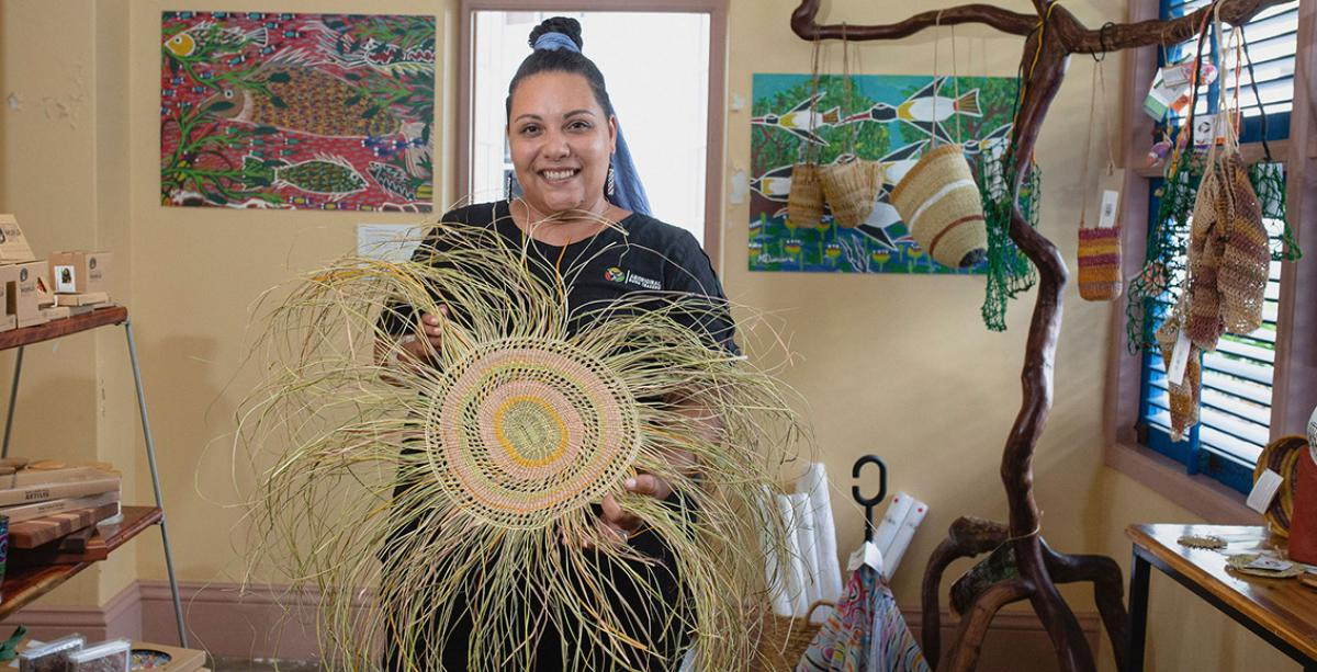 Woman holding Aboriginal weaving