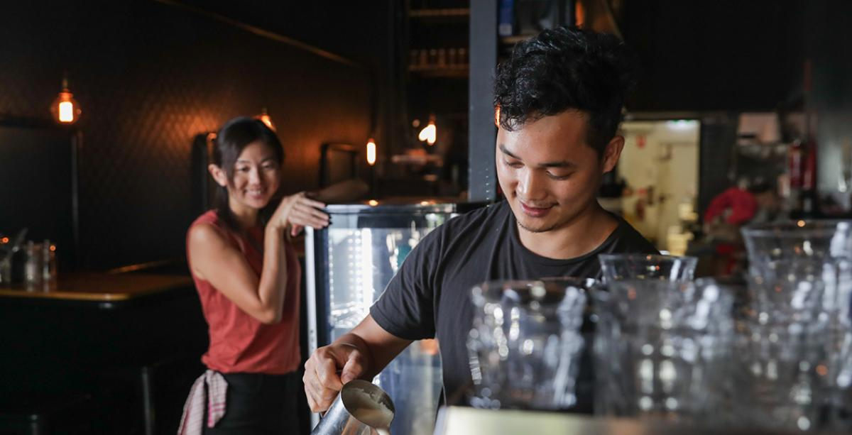 Man pouring coffee with waitress in background
