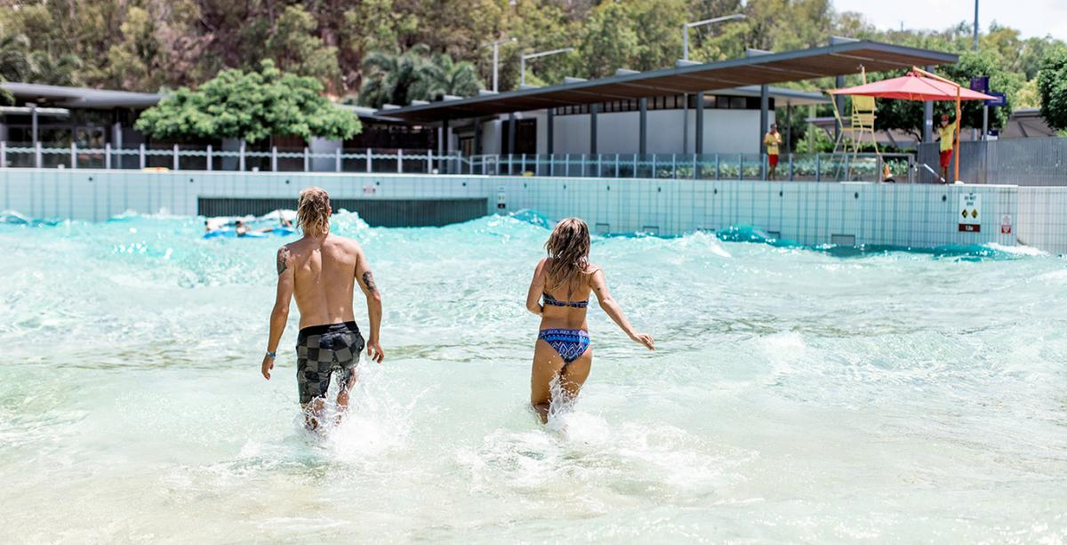 Man and woman walking into wave lagoon