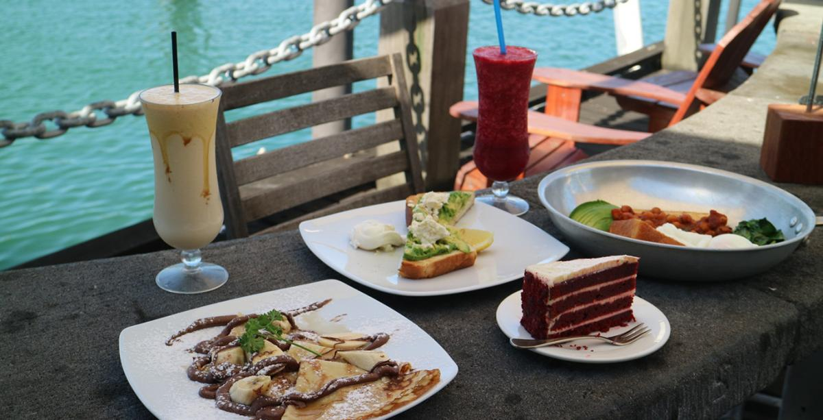 A delicious selection of food sitting on a table in a waterfront setting